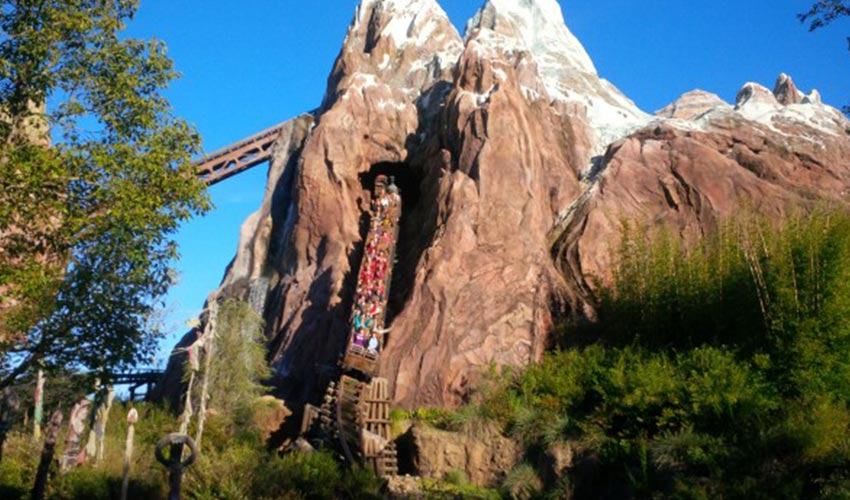 A roller coaster ride going through a mountain at Disney.