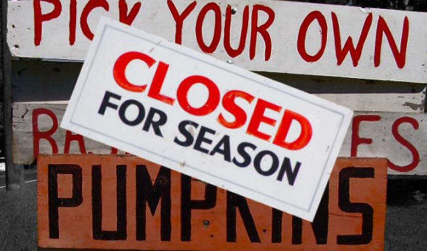 "A sign at a fruit stand that says: ""closed for season""."