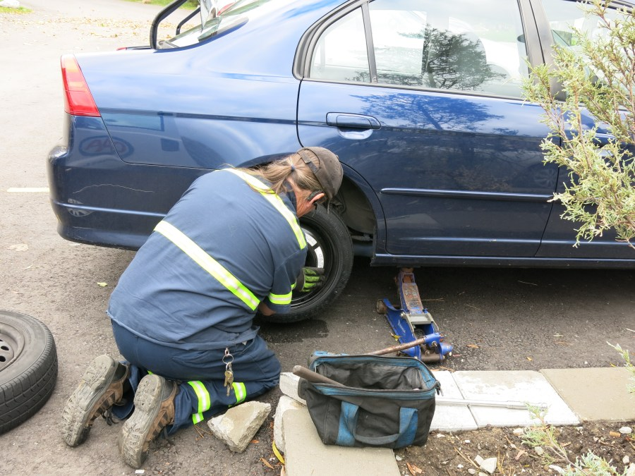 Bill locates the spare tire, checks the tire pressure and properly inflates it before replacing the flat.