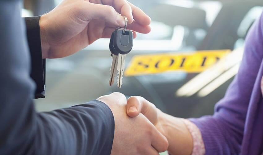 Close up of a car salesman holding car key with one hand and shaking the hand of a customer with another.