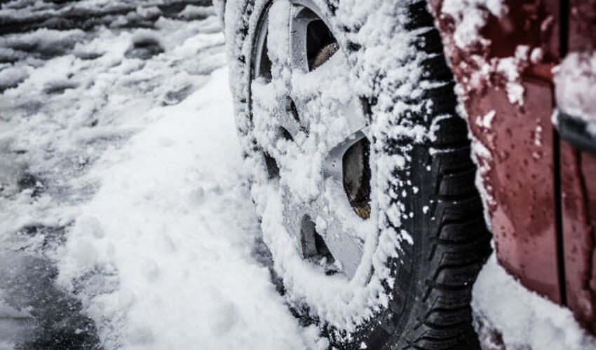 Close up of snow on car tires.