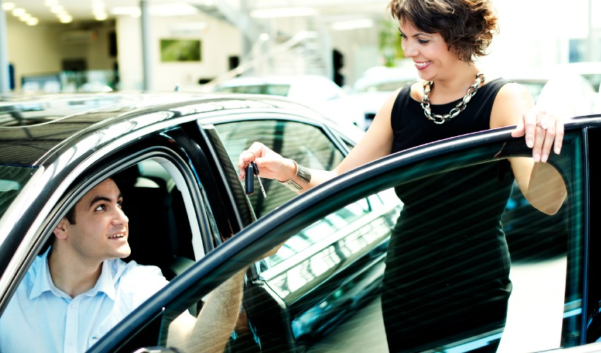 Sales woman handing over keys of new car to owner.
