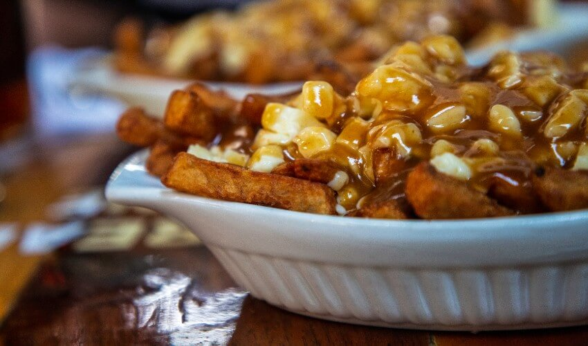 Close-up of poutine fries, cheese curds and gravy in a bowl.