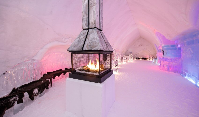 Quebec Ice Hotel interior hallway with a fireplace and ice sculptures.