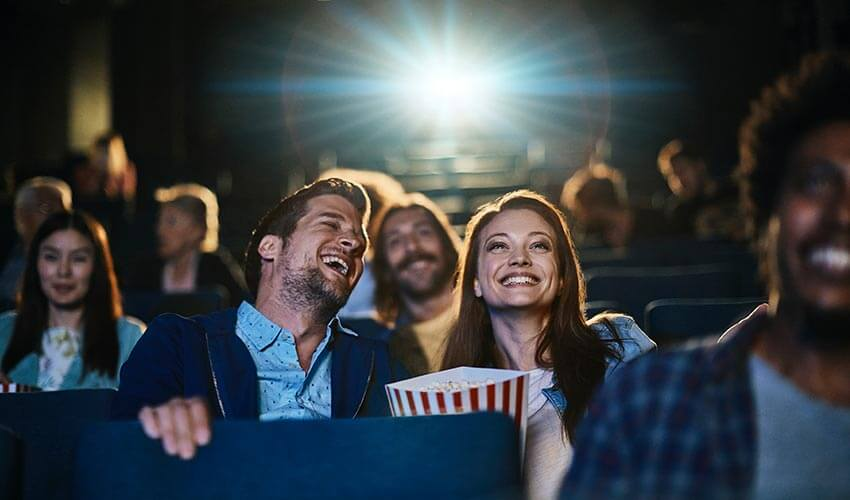 A couple watching a movie and eating popcorn in a cinema