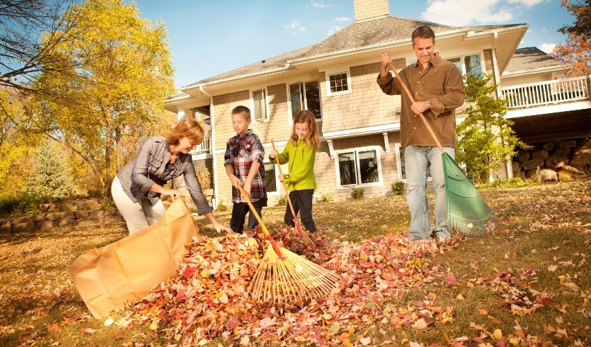 Two children helping family rake fall leaves in backyard.