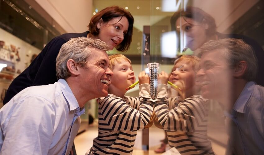 Family looking at artifacts in a glass case in a museum.