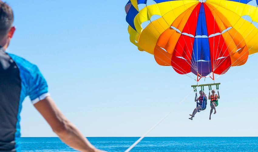 Couple parasailing in Dominicana beach in summer.