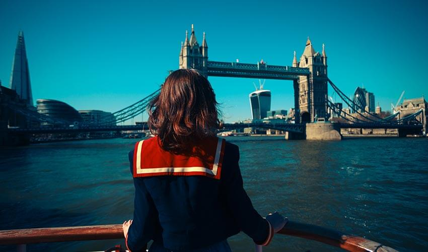 Woman on a boat is looking at Tower bridge and the London skyline