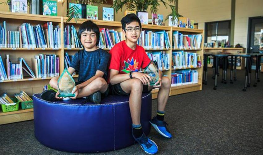 CAA School Safety Patrollers, Justin and Jonathan Zhou sitting in a library.