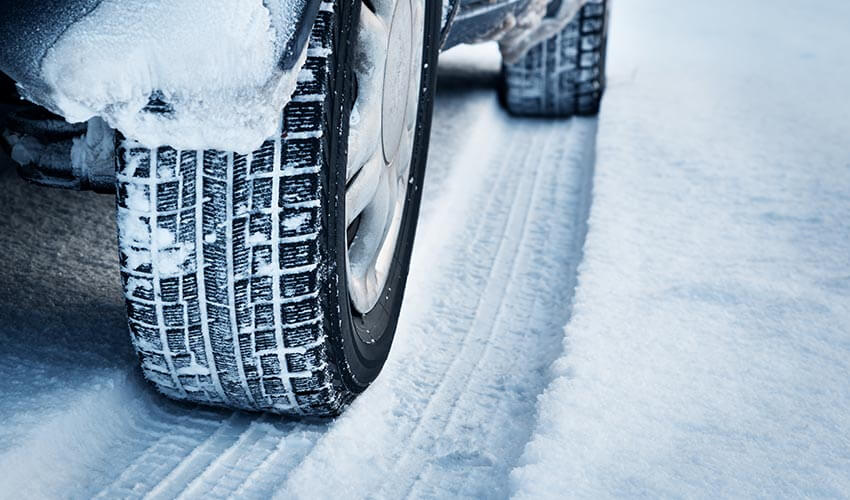 Closeup of car tires in winter on the road covered with snow.