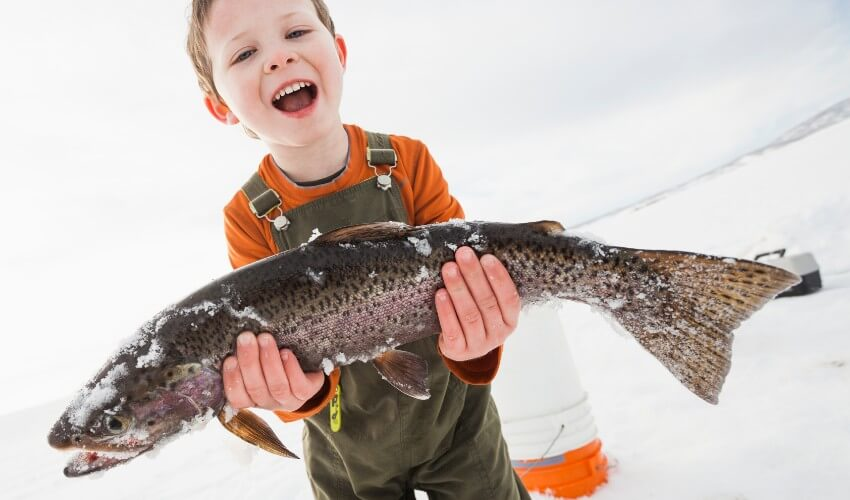 Boy holding fish in snow.