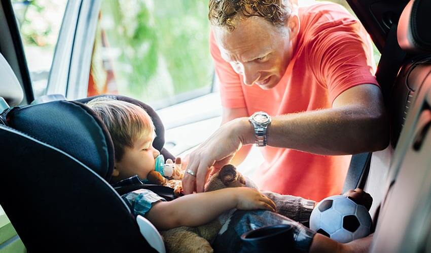 Father putting on seatbelt for son in car seat.