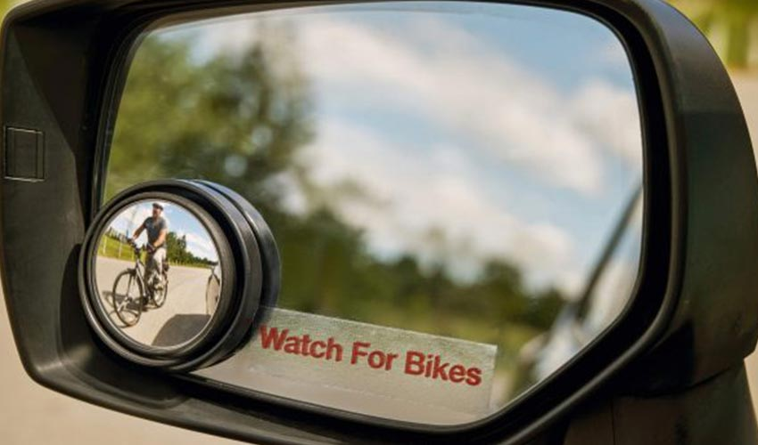 A vehicle's side mirror with a Watch For Bikes decal.