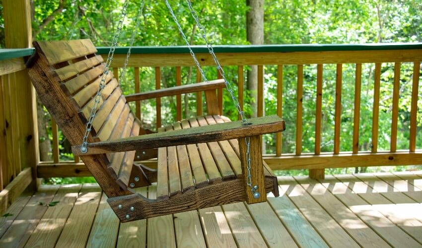 Wooden bench swing on the front porch.