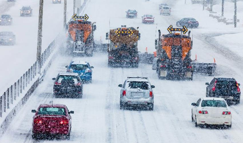 Three snow plow trucks clearing snow from a busy street with cars behind them.