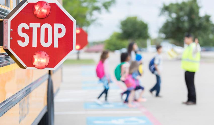 Detailed view of a stop sign on a school bus, with children crossing a screen in the background.