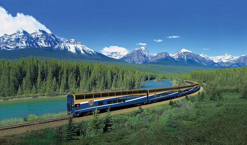 A Rocky Mountaineer train with mountains and river in the background.