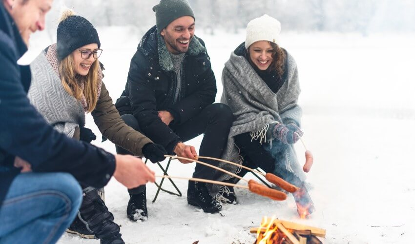 Four friends enjoying barbecue on a snowy day.
