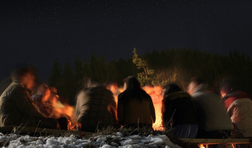 Group of people sitting around an open fire.