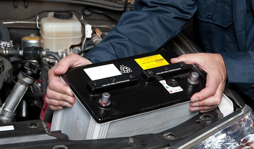 A mechanic installing a new car battery.