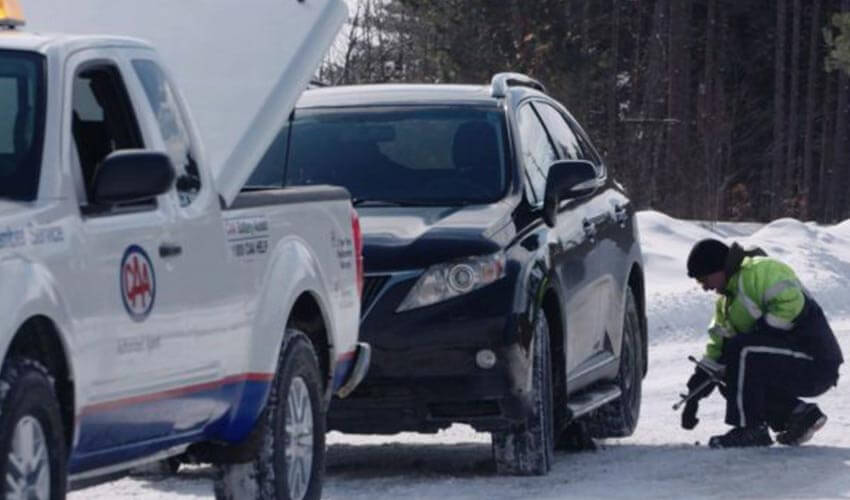 CAA driver providing roadside assistance to a black SUV in winter.