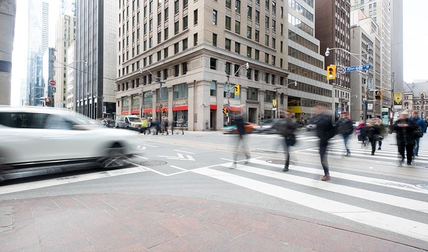 Pedestrians crossing a busy intersection in downtown Toronto.