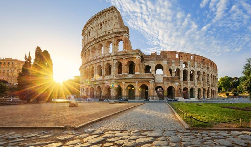 Low angle view of the Colosseum with sun in background.