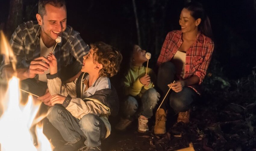 Happy family camping and eating marshmallows by a bonfire.