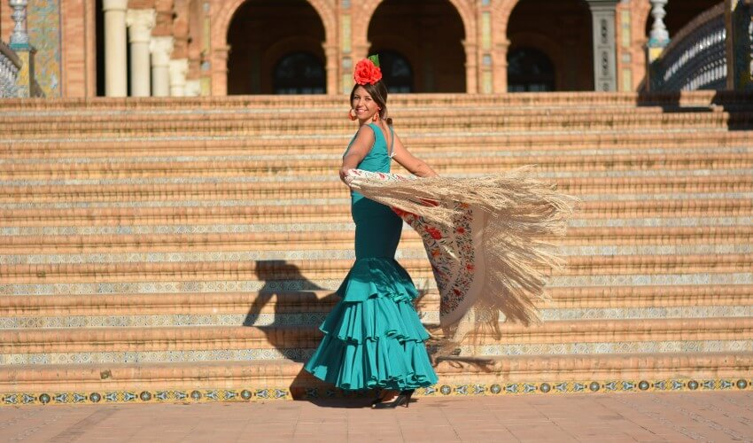 Woman dancing flamenco with a green dress in Plaza de España, in Seville, Spain.