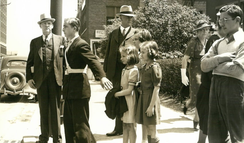 Historic photo of CAA School Safety Patroller helping peers cross the street.