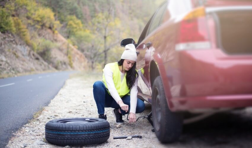 A woman fixing a flat tire on the side of the road.