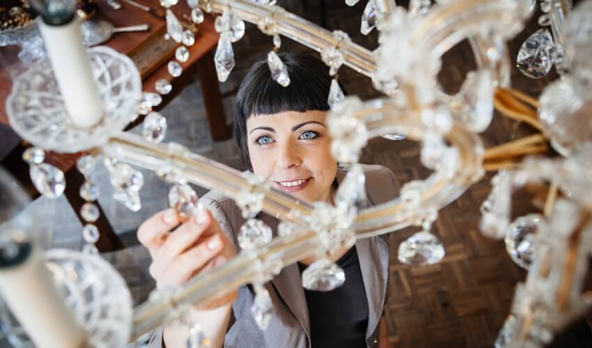 Woman looking at an antique chandelier.
