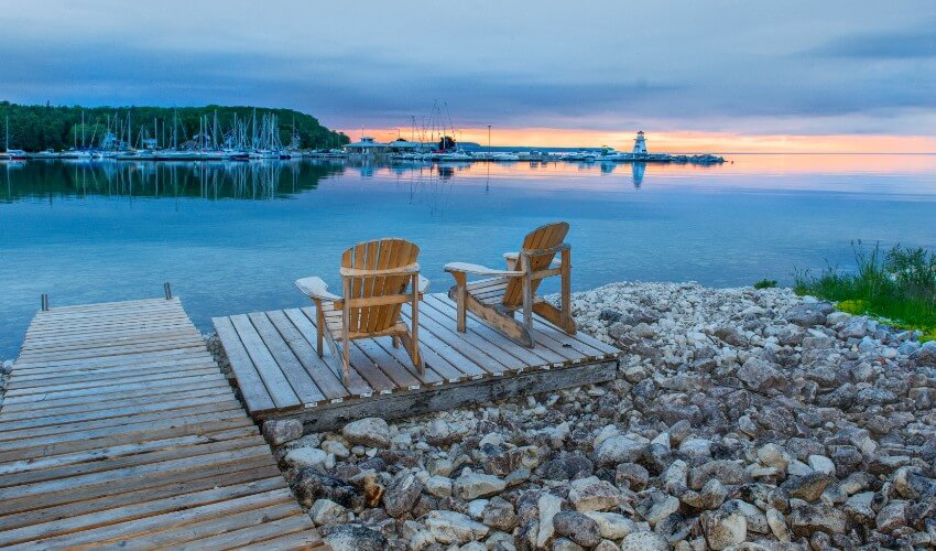 Two Adirondack chairs on a dock looking towards a marina and lighthouse at sunset.