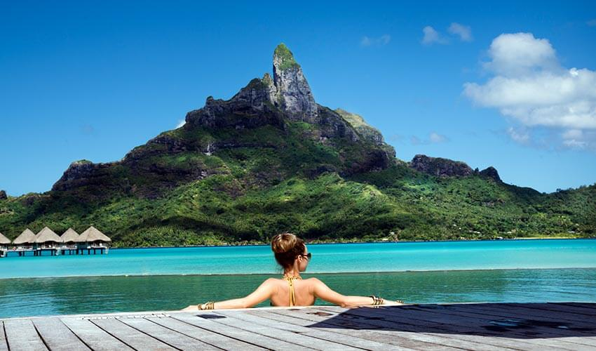 Woman lounging in a pool overlooking Otemanu Mountain in Bora Bora