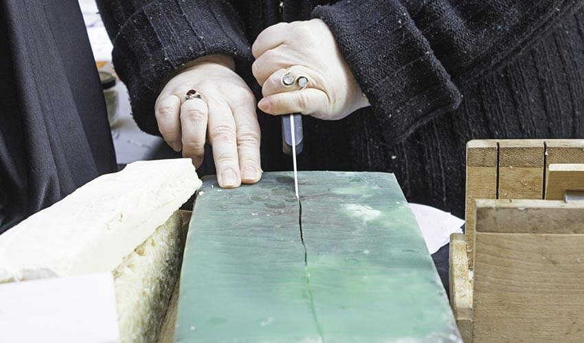 Person cutting a block of olive oil soap with knife