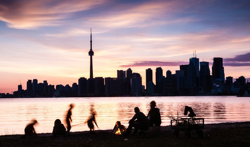 Family picnic on the shore of Toronto Island with the Toronto skyline at dusk.