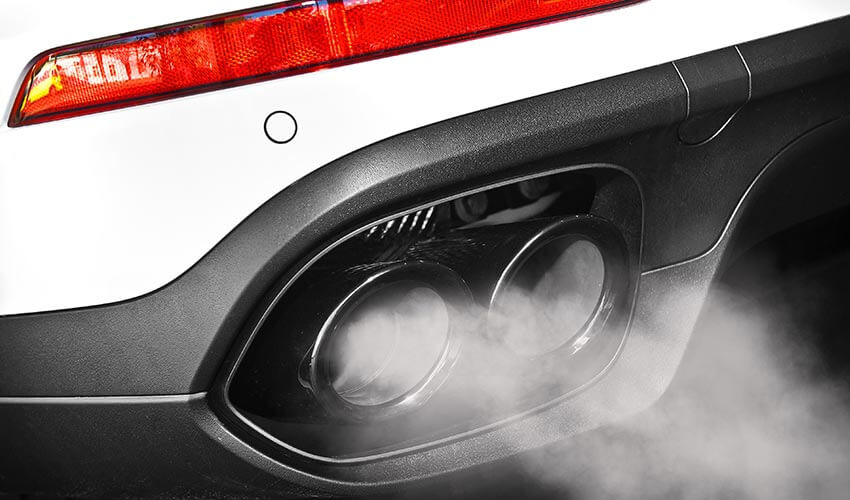 Exhaust pipes on a white car with smoke emitting.
