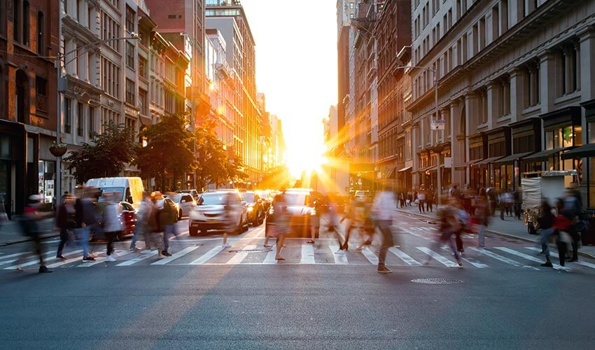 Pedestrians crossing a busy street with sunset in the background.