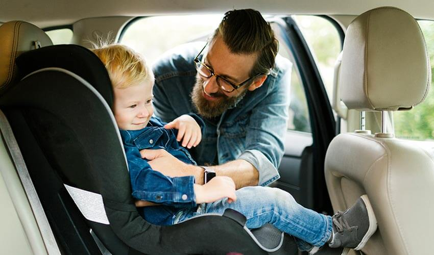 Father putting his son into car seat.