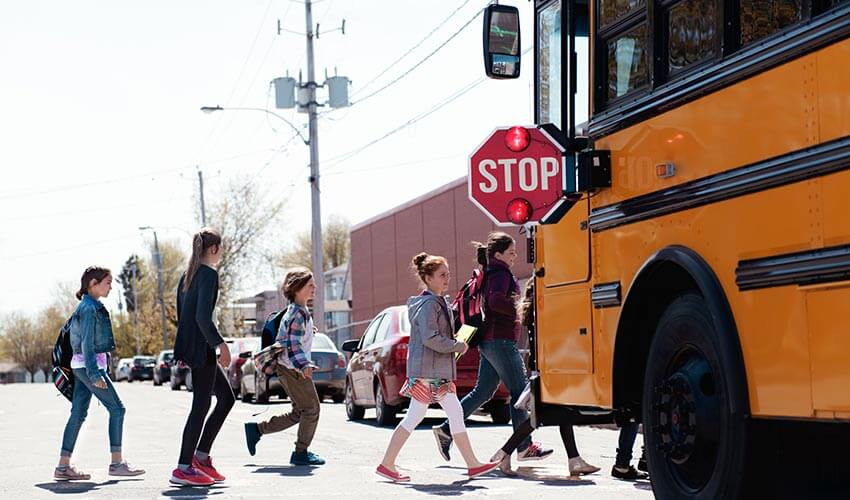 Children crossing a street in front of school bus.