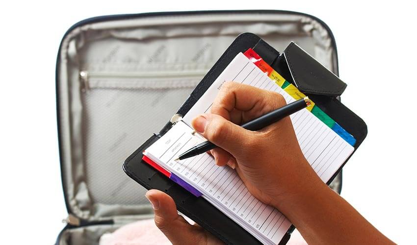 Writing out a packing list in a planner with suitcase in background.