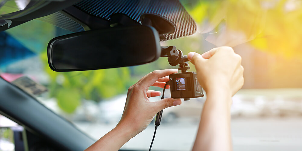 Hands are shown setting up a dash cam attached to a car's rearview mirror