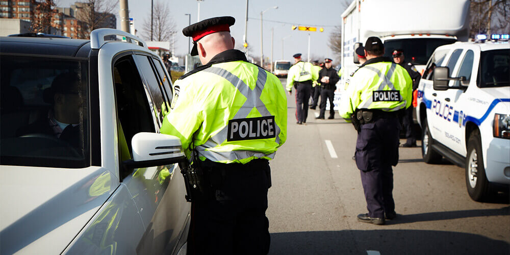 Two police officers in high-visibility jackets doing safety checks on a road in Ontario