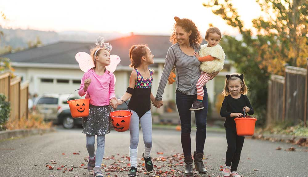 Woman with four young children dressed up as fairy and cat with buckets for trick-or-treating