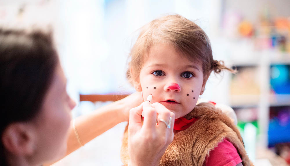 Woman painting young girl's face with whiskers for Halloween