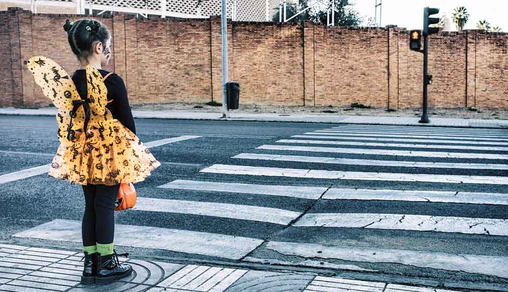 Child dressed as a butterfly for Halloween waiting to cross at crosswalk