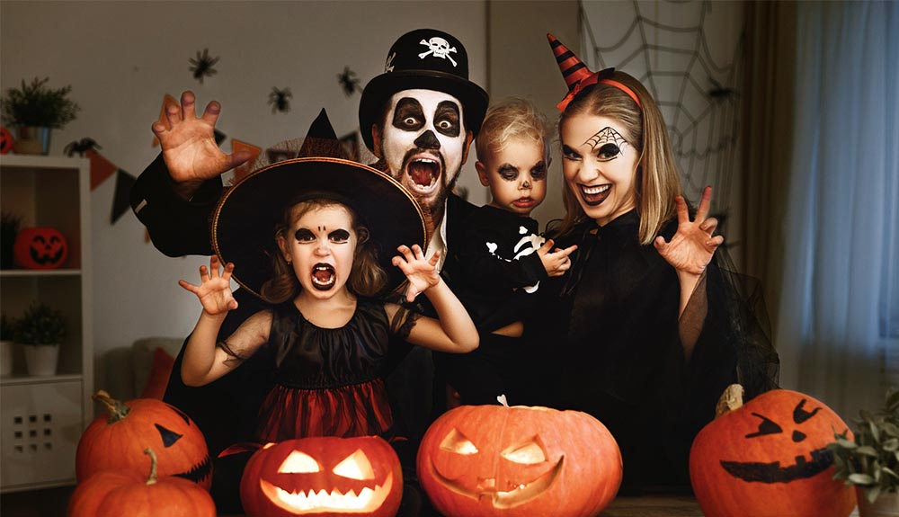 Parents and two children dressed as witches and ghouls for Halloween smiling with jack'o'lanterns