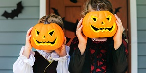 Two children covering their faces with small carved grinning pumpkins