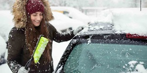 A woman scrapes her windshield on a snowy street
